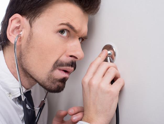 Hombre usando un estetoscopio para escuchar conversaciones, chismes.