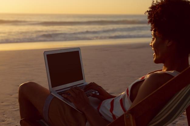 Hombre usando laptop mientras se relaja en una silla de playa en la playa