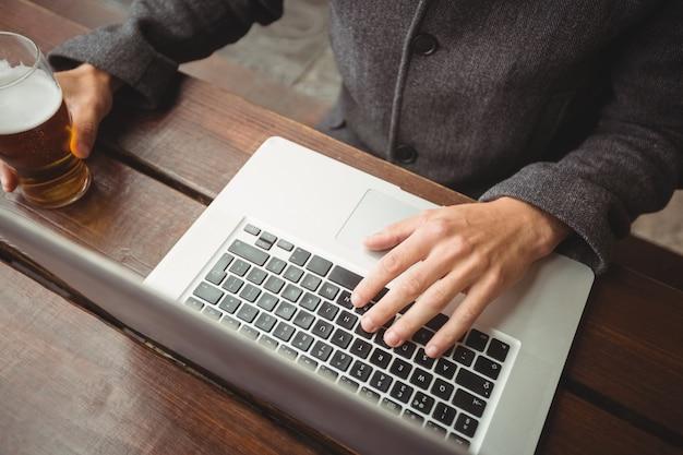 Hombre usando laptop mientras tomando un vaso de cerveza en el bar