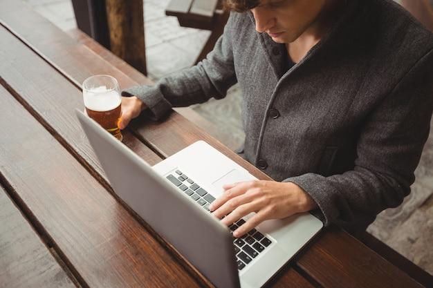 Hombre usando laptop mientras tomando un vaso de cerveza