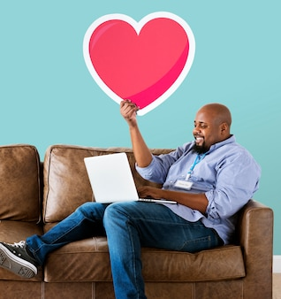 Hombre usando una laptop y sosteniendo un emoticon de corazón