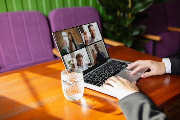 Hombre usando laptop para videollamada mientras bebe agua