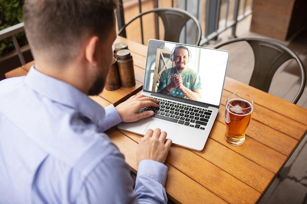 Hombre usando laptop para videollamada mientras bebe una cerveza