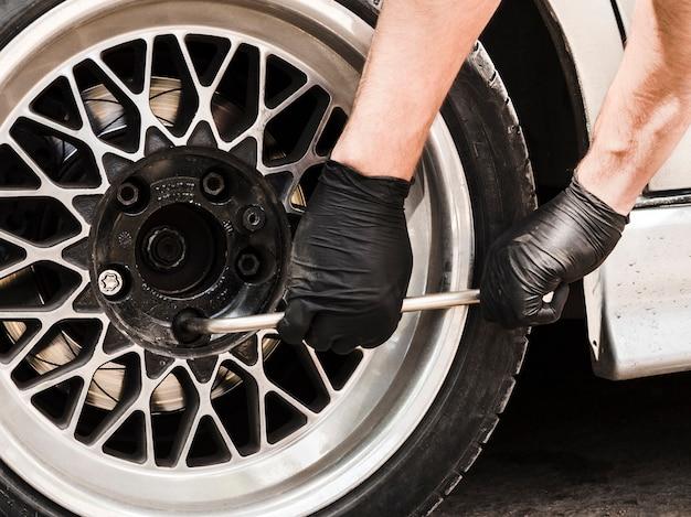 Hombre usando una llave para apretar las tuercas de la rueda