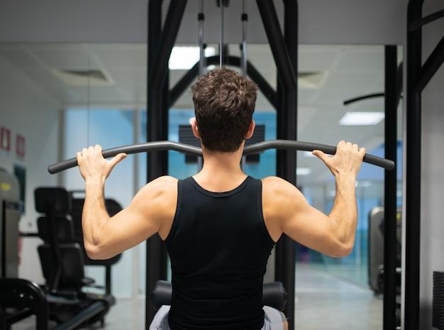 Hombre usando una máquina de lat en un gimnasio para entrenar sus hombros y espalda