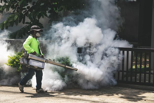 Hombre usando una máquina de nebulización para controlar los mosquitos peligrosos