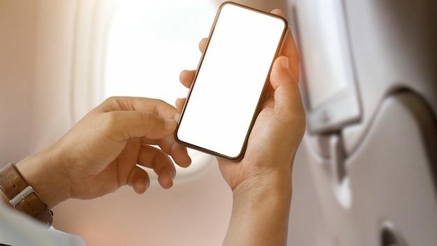 Hombre usando la pantalla en blanco del teléfono inteligente en el avión