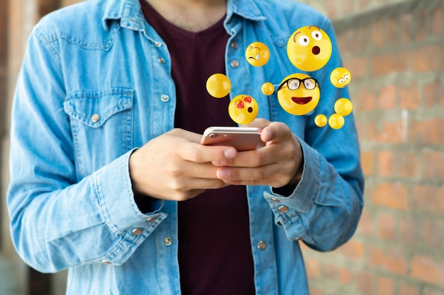 Hombre usando smartphone enviando emojis