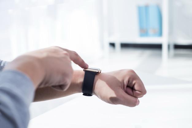 Hombre usando su aplicación de reloj inteligente. primer plano, manos