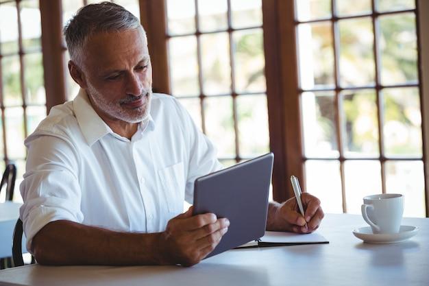 Hombre usando tableta y cuaderno
