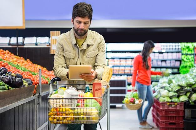 Hombre usando tableta digital mientras compras
