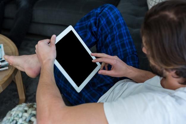 Hombre usando tableta digital en sala de estar