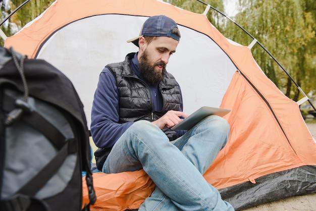 Hombre usando tableta digital en tienda de campaña
