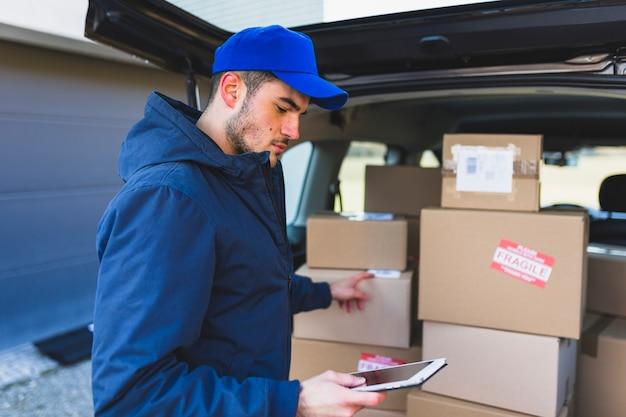 Hombre usando tableta y entregando cajas
