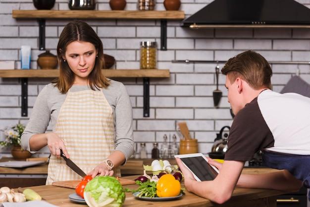 Hombre usando tableta mientras novia cortando verduras