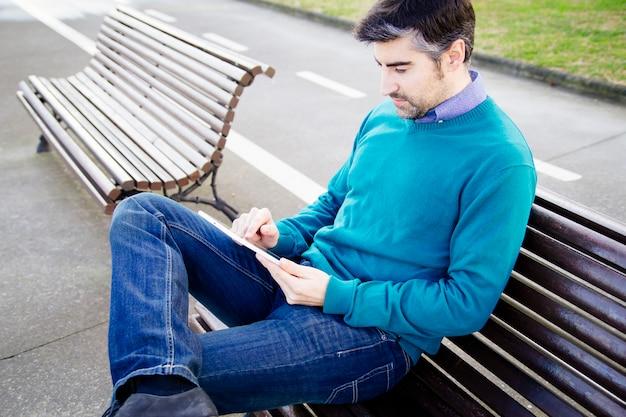 Hombre usando tableta en el parque