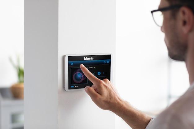 Hombre usando una tableta en su casa inteligente Foto gratis