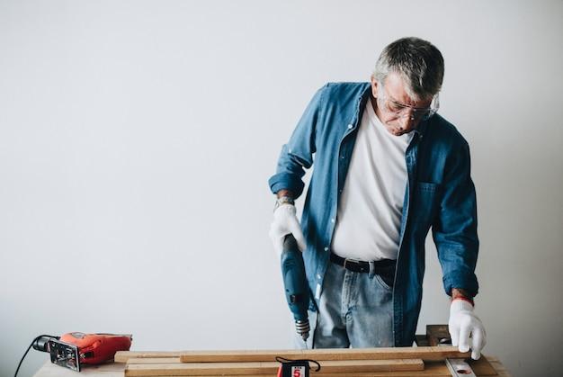 Hombre usando un taladro de mano con un tablón