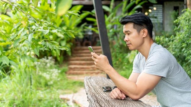 Hombre usando un teléfono inteligente en un balcón