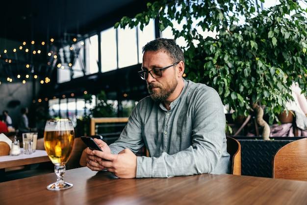 Hombre usando un teléfono inteligente en la barra.