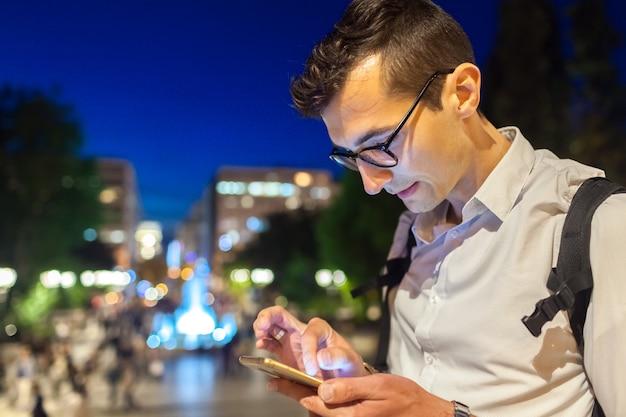 Hombre usando un teléfono inteligente en la calle de la ciudad