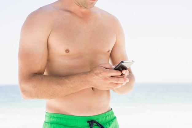Hombre usando un teléfono inteligente en la playa