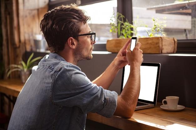 Hombre usando teléfono inteligente sentado