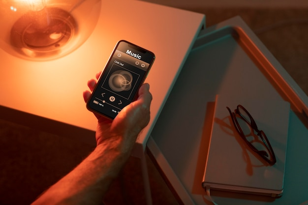 Hombre usando un teléfono inteligente en su hogar automatizado