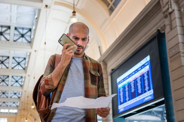 Hombre usando teléfono y mapa para orientar