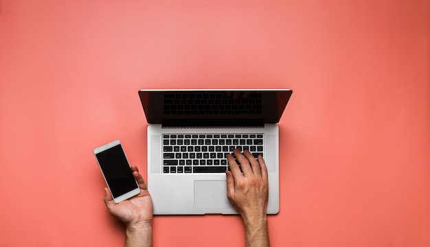 Hombre usando teléfono móvil y computadora portátil simultáneamente sobre fondo rosa pastel