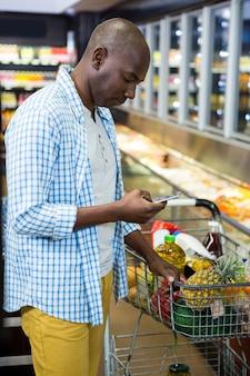 Hombre usando un teléfono móvil en la sección de comestibles mientras compra