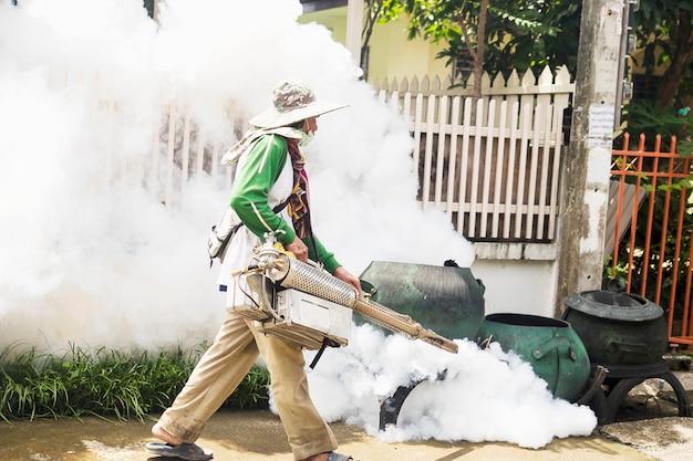 El hombre está utilizando una máquina de niebla térmica para proteger la propagación de mosquitos.