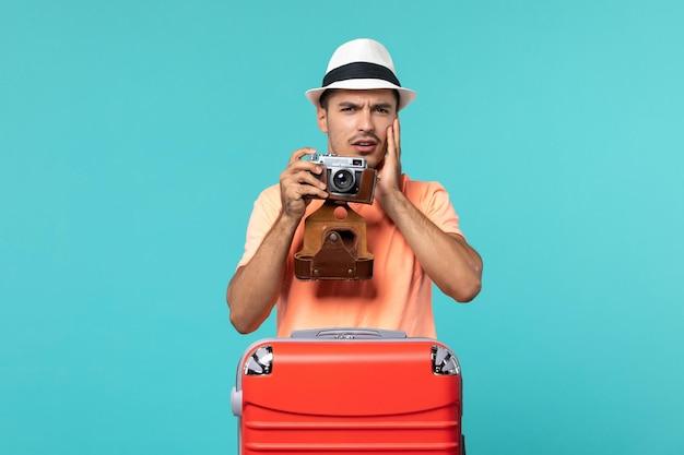 Hombre de vacaciones con su maleta roja tomando fotos con cámara en azul