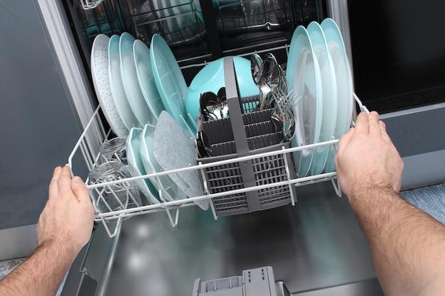 Hombre vaciar el lavavajillas en la cocina. primer plano de manos masculinas cargando platos al lavavajillas