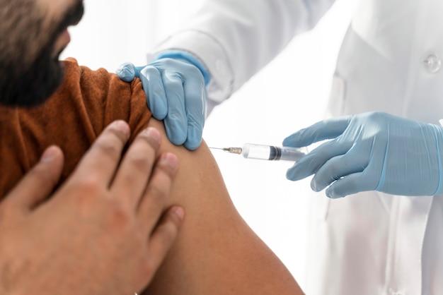 El hombre está vacunando por un médico de cerca
