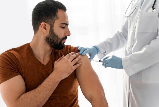 El hombre está vacunando por un médico
