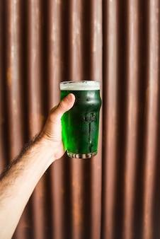 Hombre con vaso de bebida verde junto a pared de madera