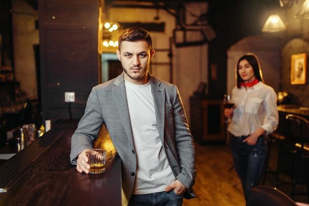 Hombre con vaso de bebidas alcohólicas en barra de bar de madera, mujer atractiva con vino tinto de fondo. ocios de pareja en pub