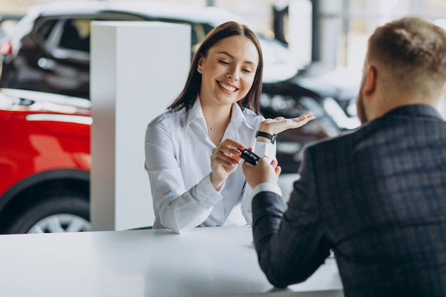 Hombre con vendedora en sala de exposición de coches