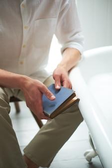 El hombre de la vendimia en manos brillantes de la ropa sostiene un libro cerrado con el espacio vacío para la copia o el texto