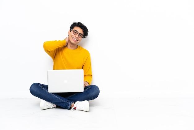 Hombre venezolano sentado en el suelo con laptop riendo