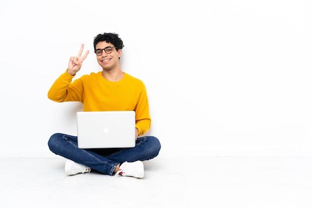 Hombre venezolano sentado en el suelo con laptop sonriendo y mostrando el signo de la victoria