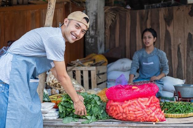 Hombre verdulero sonrió mientras se inclinaba sosteniendo la espinaca en el mercado tradicional