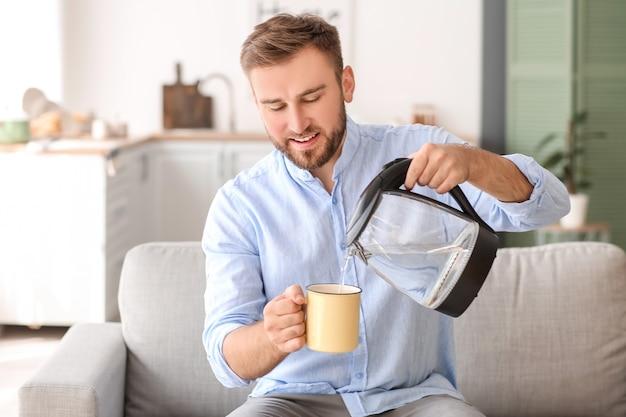 Hombre vertiendo agua hervida caliente de hervidor eléctrico en taza en casa