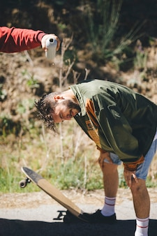 Hombre vertiendo agua sobre la cabeza de un amigo
