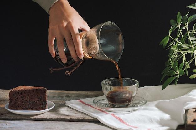 Hombre vertiendo café frío en vaso en la mesa