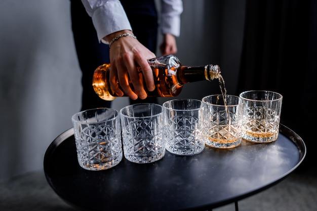 El hombre está vertiendo la fuerte bebida alcohólica en el vaso