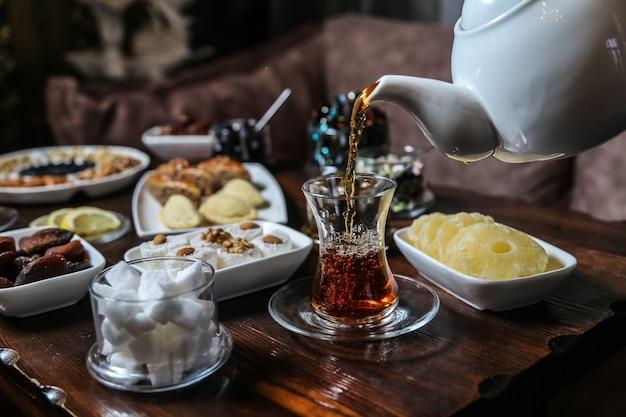 Hombre vertiendo té en armudy juego de té de frutas secas de azúcar vista lateral
