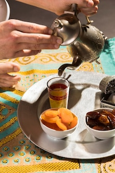 Hombre vertiendo té en pequeña taza alta vista