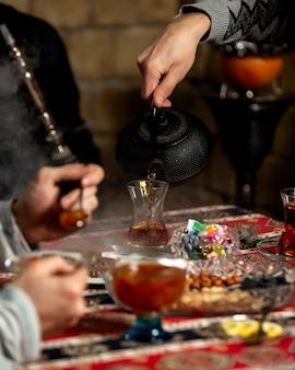Hombre vertiendo té en vidrio armudu en configuración de té tradicional azerbaiyano